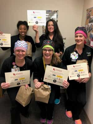 healthcare workers holding up meals gifted from Morris & Dewett as a thank you gift and certificates