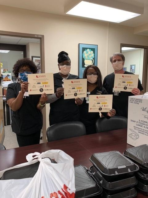 Staff of Morris & Dewett all wearing masks and holding certificates